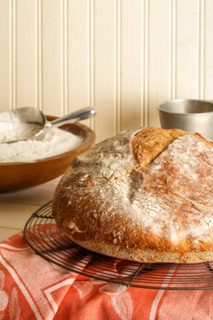 A round rustic artisan bread cools on a wire baking rack resting on a sunlit table surrounded by baking utensils and a bowl of flour  photo