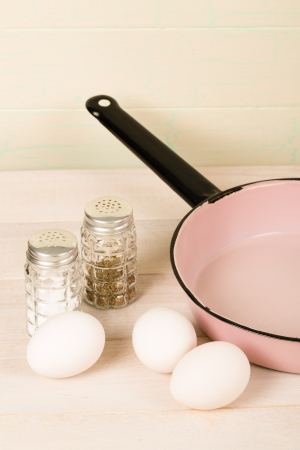 Three white whole egss rest on a table next to a vintage pink and black enamel frying pan with old-fashioned salt and pepper shakers nearby