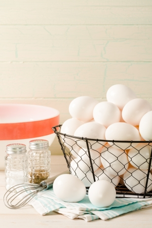 Several fresh eggs rest in a wire basket with a vintage bowl and wire whisk, accented with old-fashioned salt and pepper shakers sitting ready for preparing breakfast  Фото со стока
