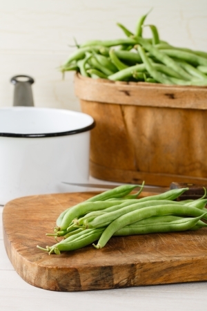 Garden fresh green beans  string beans  on a wood cutting board are ready to be prepared for a meal   A produce basket full of beans sits in the background with a white and black enamel pot