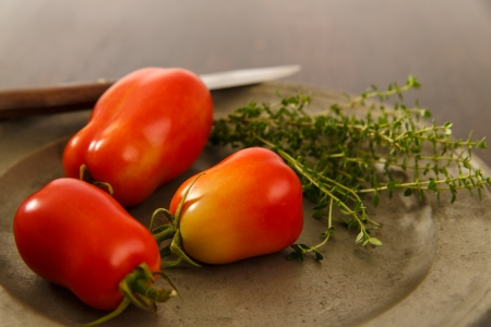 Close up view of homegrown ripe plum tomatoes on an old pewter plate accented with fresh Thyme Фото со стока