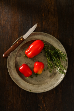 Overhead view of ripe, red plum tomatoes on a rustic pewter plate accented with Thyme   Copy space above and below