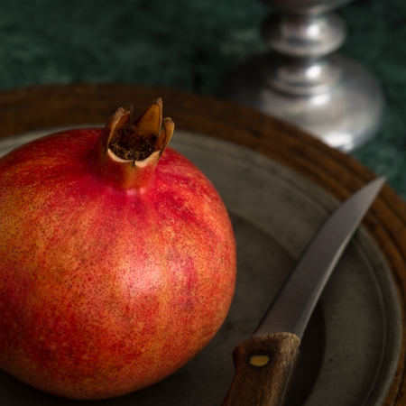 A whole red pomegranate and a knife rest on a pewter plate against a dark surface of wood and green marble   The stem of a pewter goblet is seen in the background