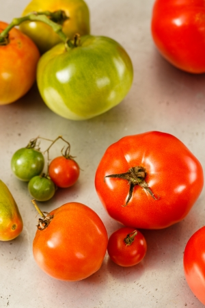 A variety of red and green heirloom variety tomatoes rest on an old, worn metal baking sheet  Фото со стока