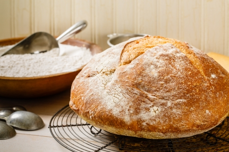 Round rustic artisan bread rests on a vintage wire cooling rack surrounded by a baking utensils and an old wood bowl full of flour photo