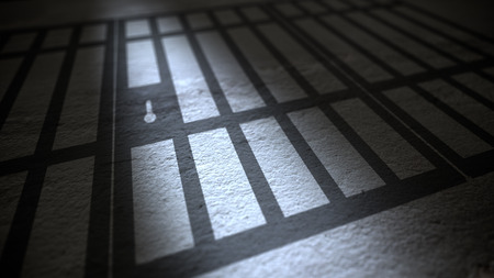 Jail cells bars casting shadows on the prison floor. Stock Photo