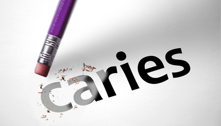 Eraser deleting the word Caries  Stock Photo