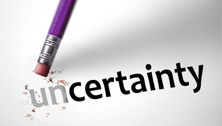 Eraser changing the word Uncertainty for Certainty  Stock Photo