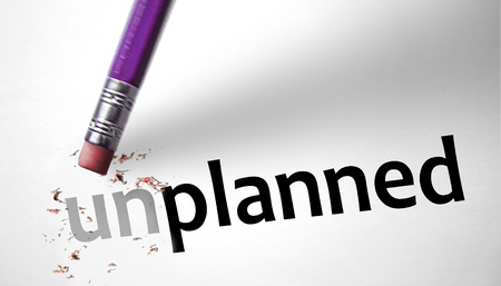 planned: Eraser changing the word Unplanned for Planned  Stock Photo