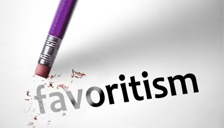 deleting: Eraser deleting the word favoritism Stock Photo