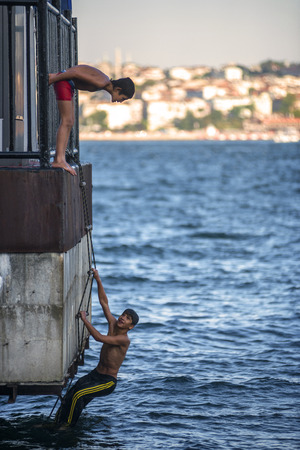 istanbul beach: ISTANBUL - AUGUST 5: Teenagers jump into Bosphorus sea from wooden pier in Istanbul, Turkey on August 5, 2014. The Bosphorus is the strait that separates the continents of Europe and Asia.