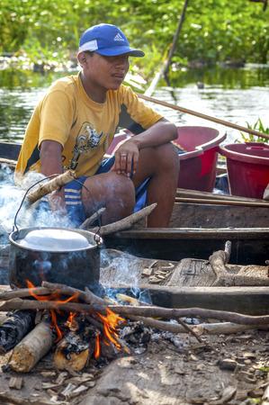 AMAZONIA, PERU - DEC 28: Unidentified Amazonian indigenous man cooking fish over a wooden raft, on December 28, 2009, in Peruvian Amazonia, Loreto, Peru, South America Redakční
