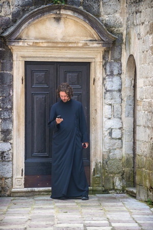 spirtual: GREECE, ATHENS - JULY 19, 2014: A priest sending a message with his cell