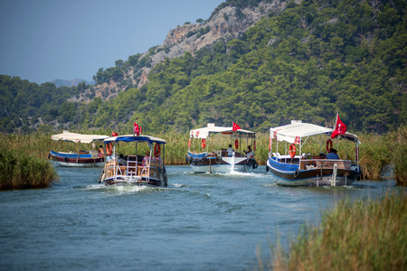 TURKEY, DALYAN, MUGLA - JULY 19, 2014: Touristic River Boats with tourists in the mouth of the Dalyan River