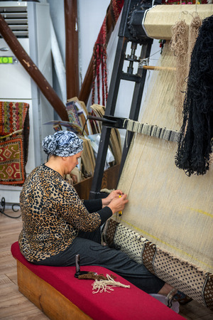 sectors: CAPPADOCIA - MAY 17 : Woman working at the manufacture of carpets, on May 17, 2013, in Cappadocia, Turkey. Turkish rugs are one of the main economic sectors of the country.