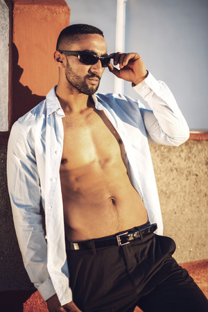 undressing: Confident attractive Arab businessman undressing