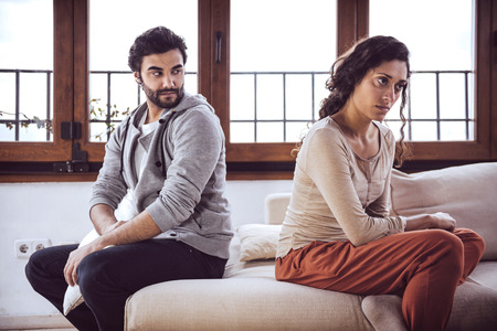 not talking: Couple not talking after a fight on the sofa in living room at home