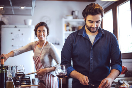 romantic dinner: Young couple cooking. Man and woman in their kitchen Stock Photo