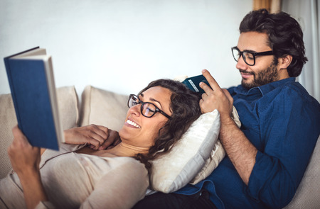 couple on couch: Young couple reading book on couch at home