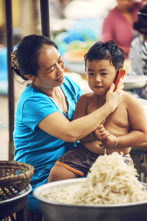 cramped: MEKONG DELTA - JUNE 14: Unidentified kid in a market with his mother, on June 14, 2015 in Mekong Delta, Vietnam Editorial