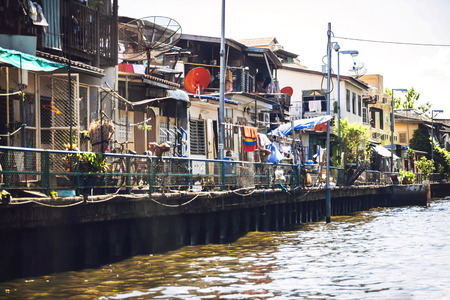 encroaching: BANGKOK - JUNE 15, 2015: Houses around Lat Phrao canal. Houses encroaching on the canal are going to be demolished to make way for embankments along both sides of the canal to prevent flooding. Editorial