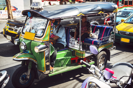 ubiquitous: BANGKOK, THAILAND - JUNE 18, 2015: Colorful example of the ubiquitous local transportation, a motorized tuktuk, drives with a client behind.