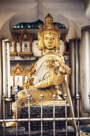 phrom: Phra Phrom statue in Bangkok a street. Phra Phrom is the Thai representation of the Hindu god Brahma Stock Photo