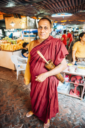 practitioners: Bangkok, Thailand - January 02, 2014: Buddhist monk in a market posing to camera. Roughly 95% of the Thai people are practitioners of Theravada Buddhism, the official religion of Thailand