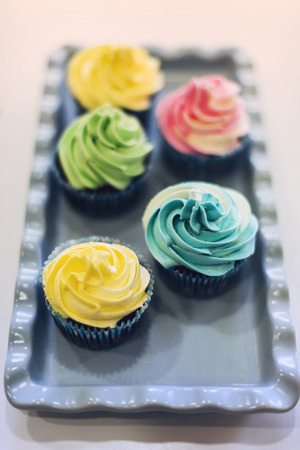 white backing: Delicious cream color cupcakes in a bakery shop