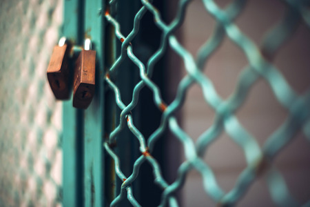 keep gate closed: Padlock on metal cage door Stock Photo