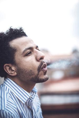 mulatto: Confident attractive mulatto man smoking a cigarrette
