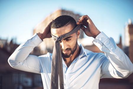 confident man: Confident attractive Arab businessman undressing