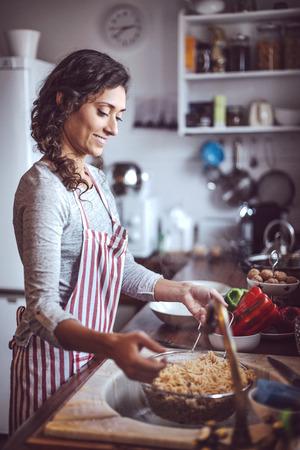 pareja comiendo: Cocción pareja joven. El hombre y la mujer en su cocina
