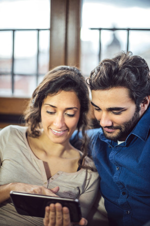 25 30 years: Young Couple Sitting On Sofa Using Digital Tablet Stock Photo