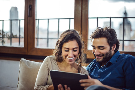 25 to 30 years old: Young Couple Sitting On Sofa Using Digital Tablet Stock Photo