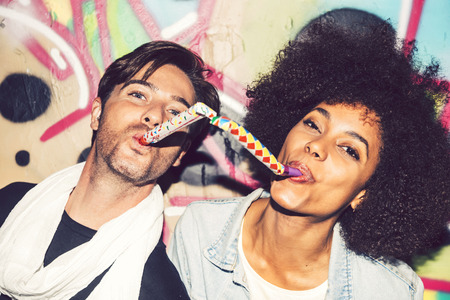 interracial couple: Interracial couple celebrating and playing with party blowers