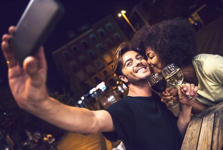 데이트 중 와인을 마시고 테라스에서 셀카를 복용하는 캐주얼 한종 인종 커플 스톡 콘텐츠