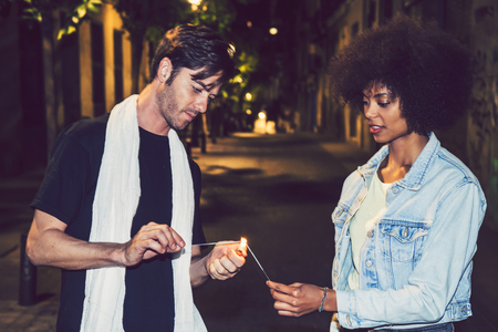 interracial couple: Interracial couple having fun with bengal lights Stock Photo