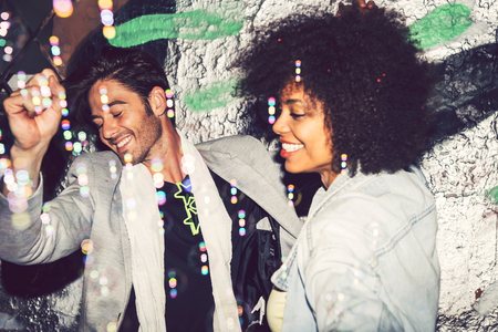 interracial couple: Happy interracial couple in a celebration with bubbles