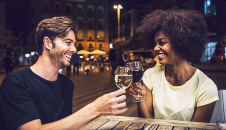 romantic date: Casual interracial couple drinking wine during date Stock Photo
