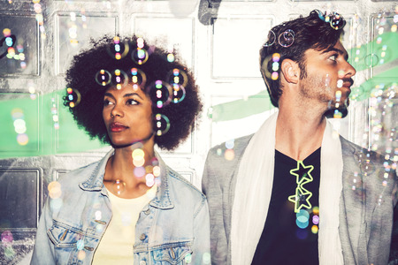 interracial couple: Sad and serious interracial couple during a celebration with bubbles Stock Photo