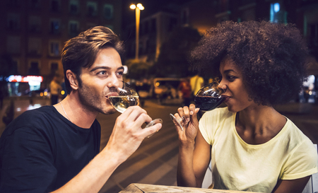 interracial couple: Casual interracial couple drinking wine during date Stock Photo