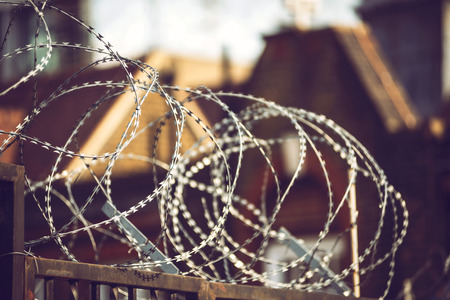 prohibido el paso: Clsoe up crop fence with barb wire on it on blurred background. Foto de archivo