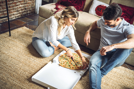 Young lovely couple sitting on floor and cutting ordered pizza.