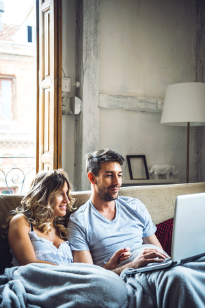 couple on couch: Two young people cuddling on sofa and laughing while watching laptop. Stock Photo