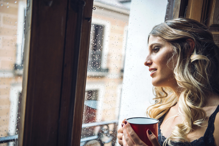 imagining: Young beautiful girl holding cup of tea and looking out window in rainy day. Stock Photo