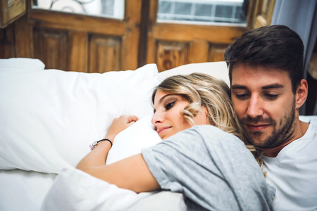 Two young people hugging in bed while having time together.