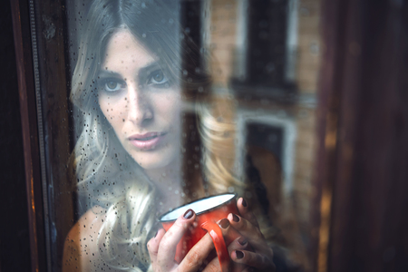 Shot through glass of young pretty female holding red mug and looking out of window at rain.