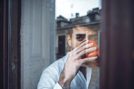 imagining: Young male in white shirt drinking tea while looking out of window in rainy day.
