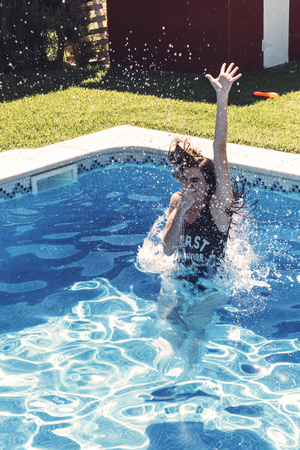 Young pretty woman closing nose and diving into pool.